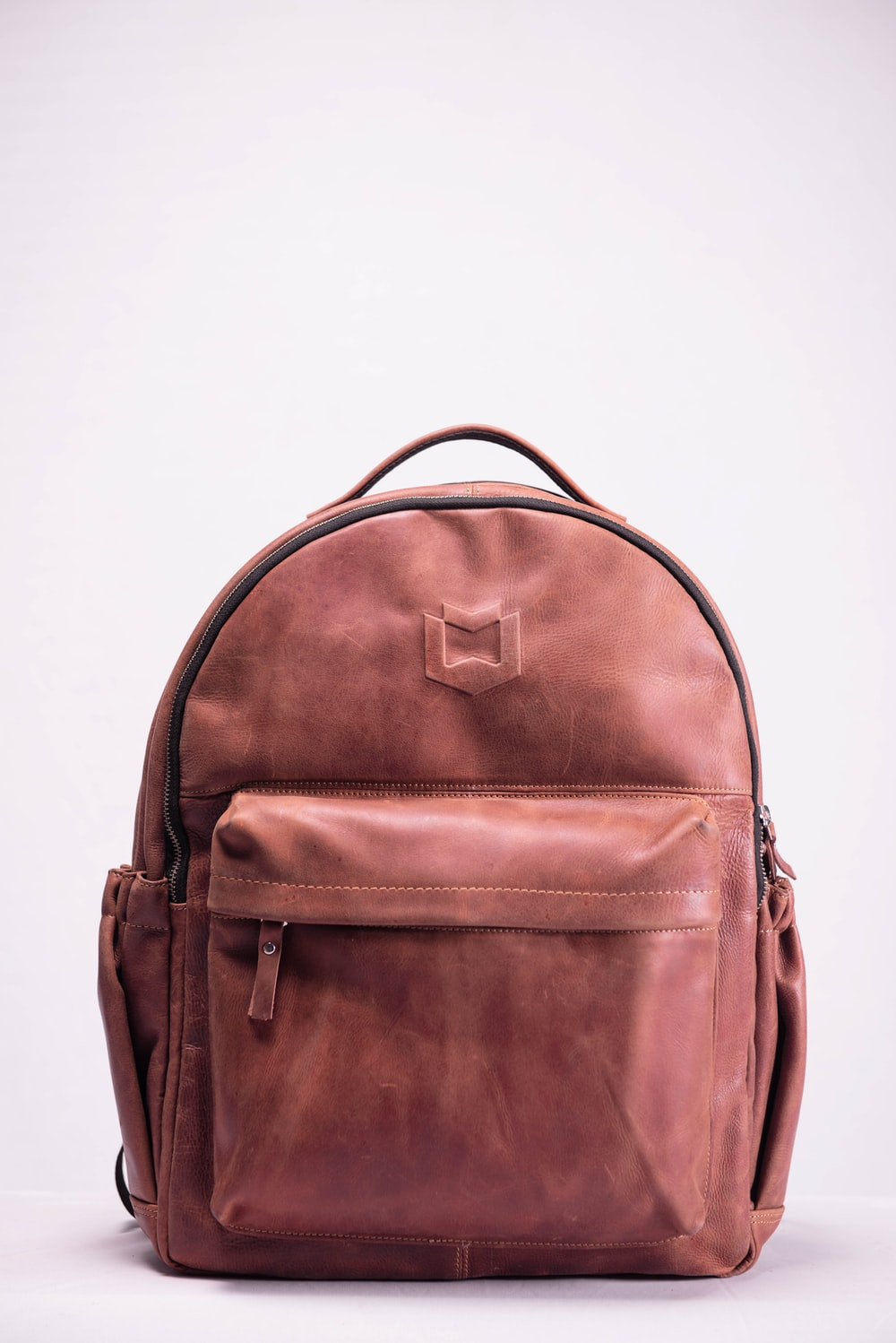 brown leather backpack on white surface