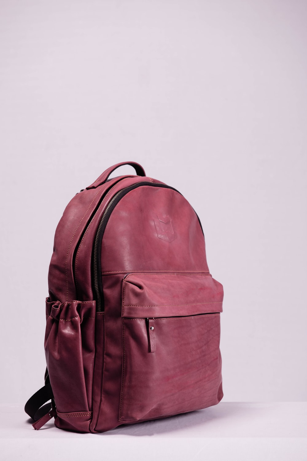 red leather backpack on white wall