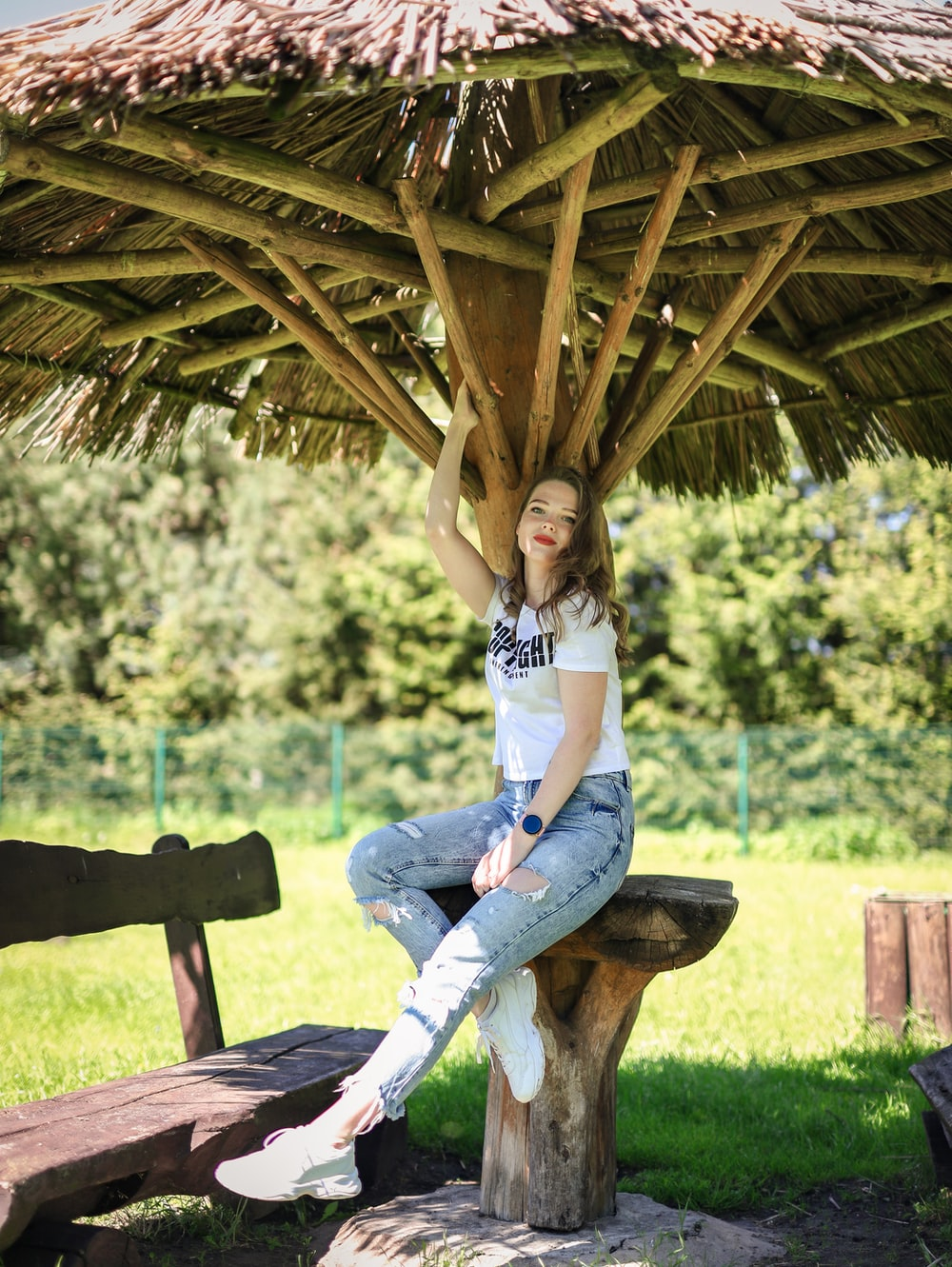 woman in white t-shirt and blue denim jeans sitting on brown wooden bench during daytime