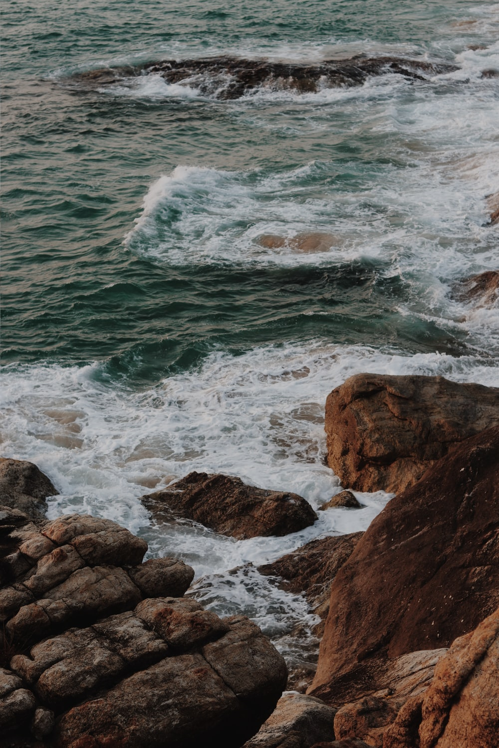 brown rocky shore with ocean waves crashing on rocks during daytime