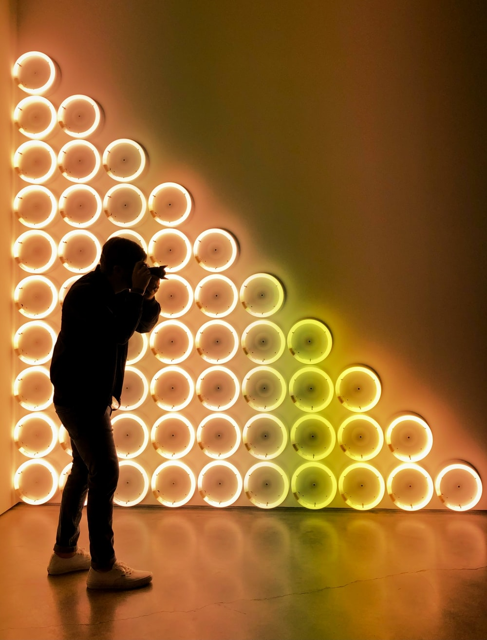 silhouette of woman standing in front of lighted wall