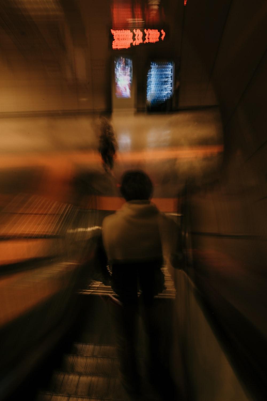 man in white shirt walking on tunnel during daytime