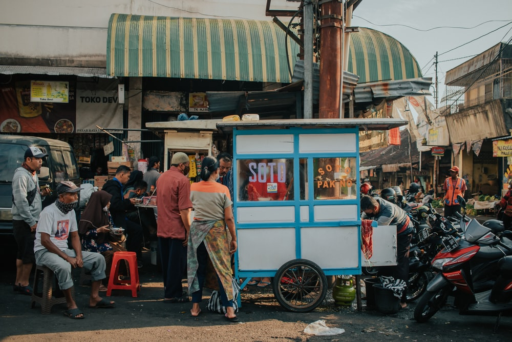 people standing near blue and white food stall during daytime