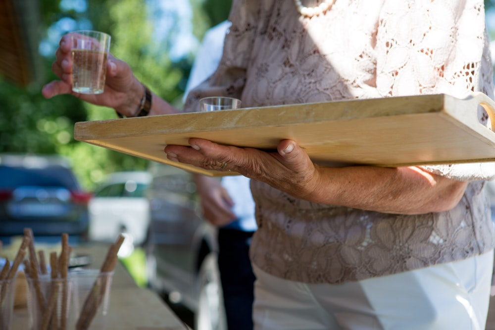 person holding brown wooden tray