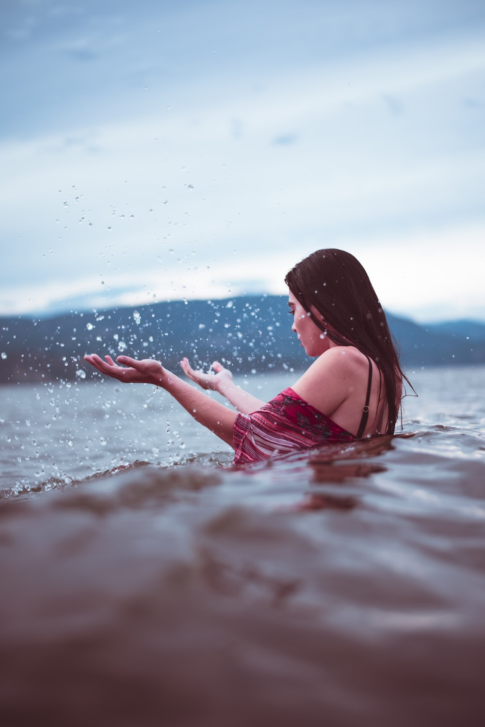 woman in red dress on water during daytime