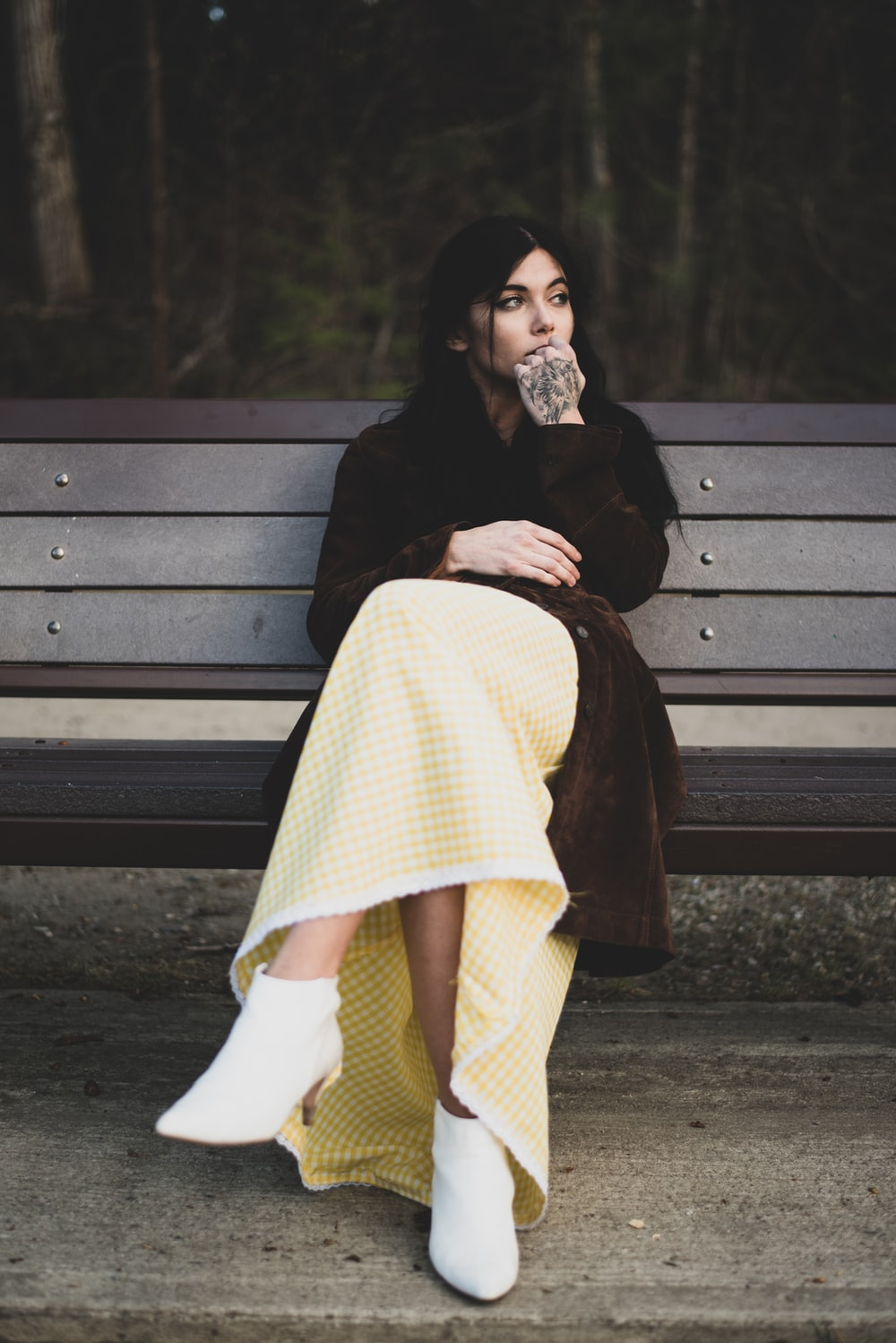 woman in black coat and white skirt sitting on brown wooden bench