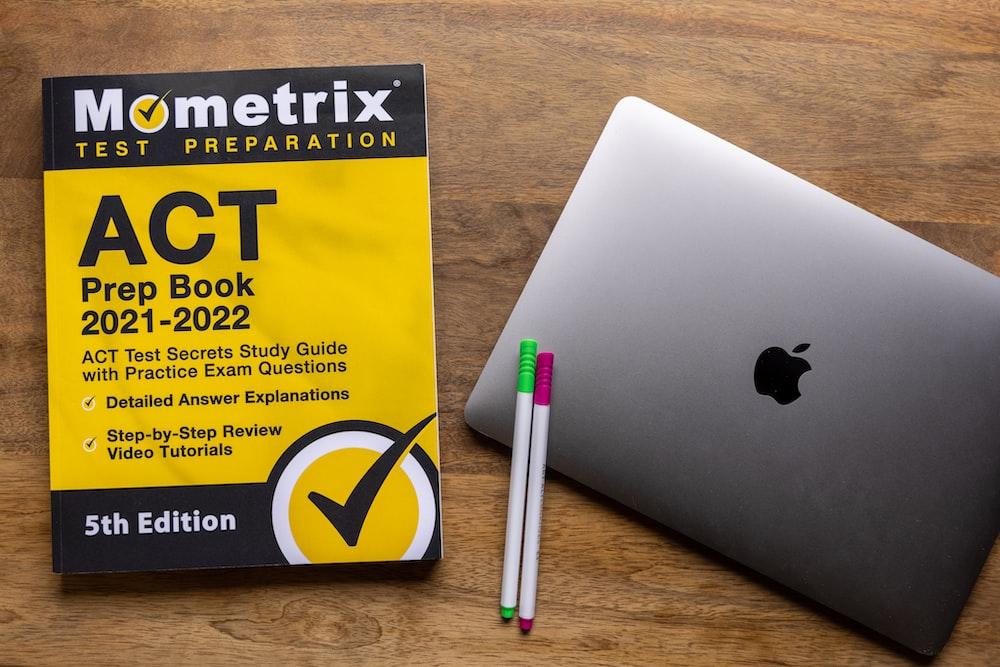 silver macbook beside white pen