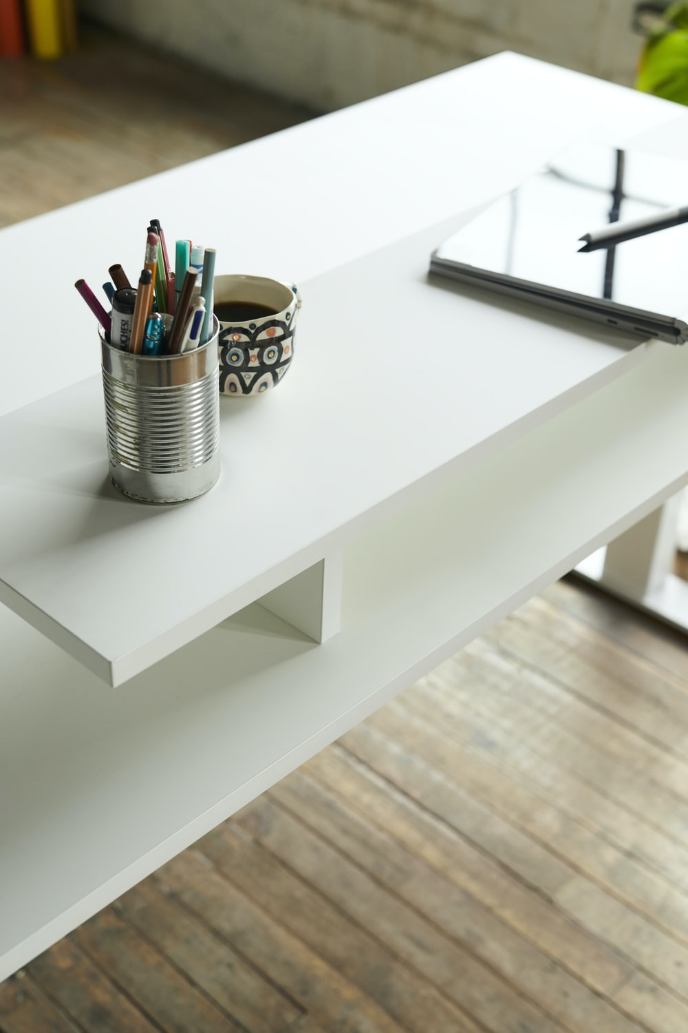 pencils in white steel cup on white wooden table