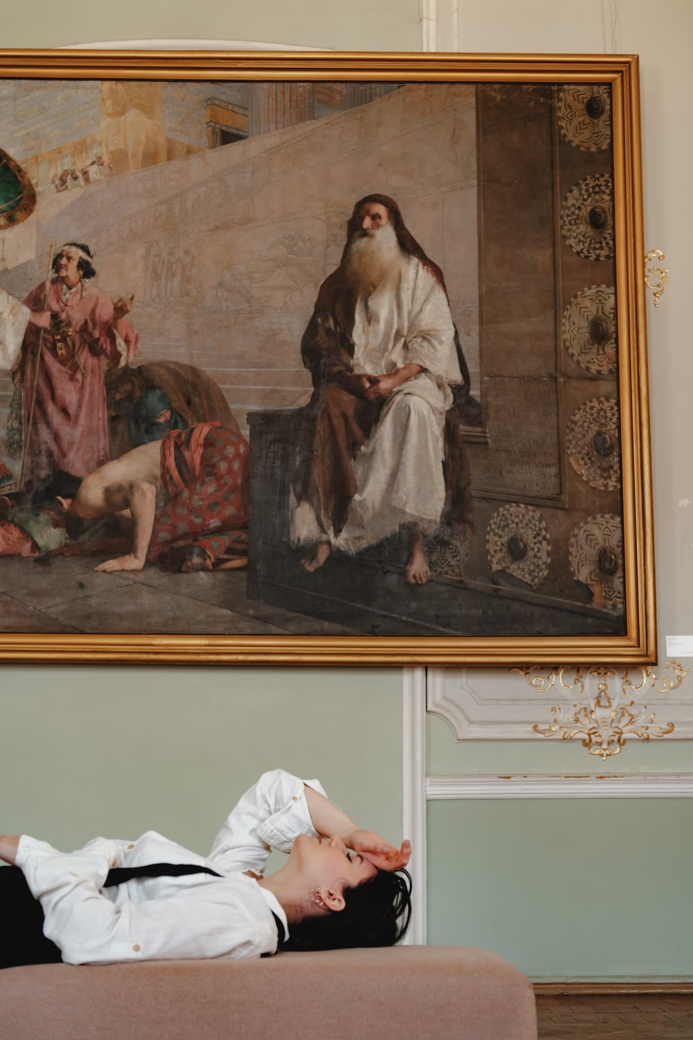 woman in white robe sitting on bed painting