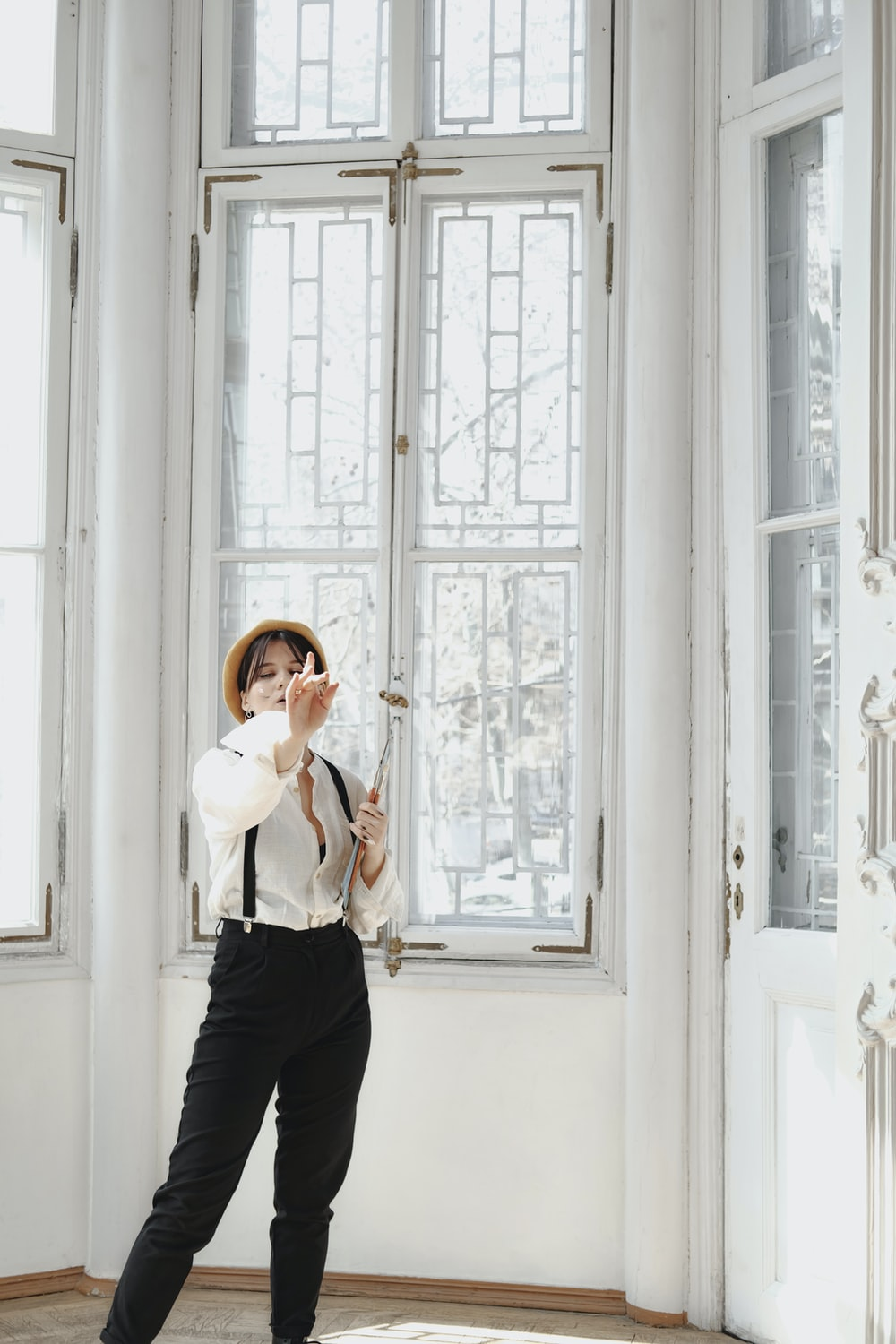 woman in white long sleeve shirt and black pants standing beside white wooden window