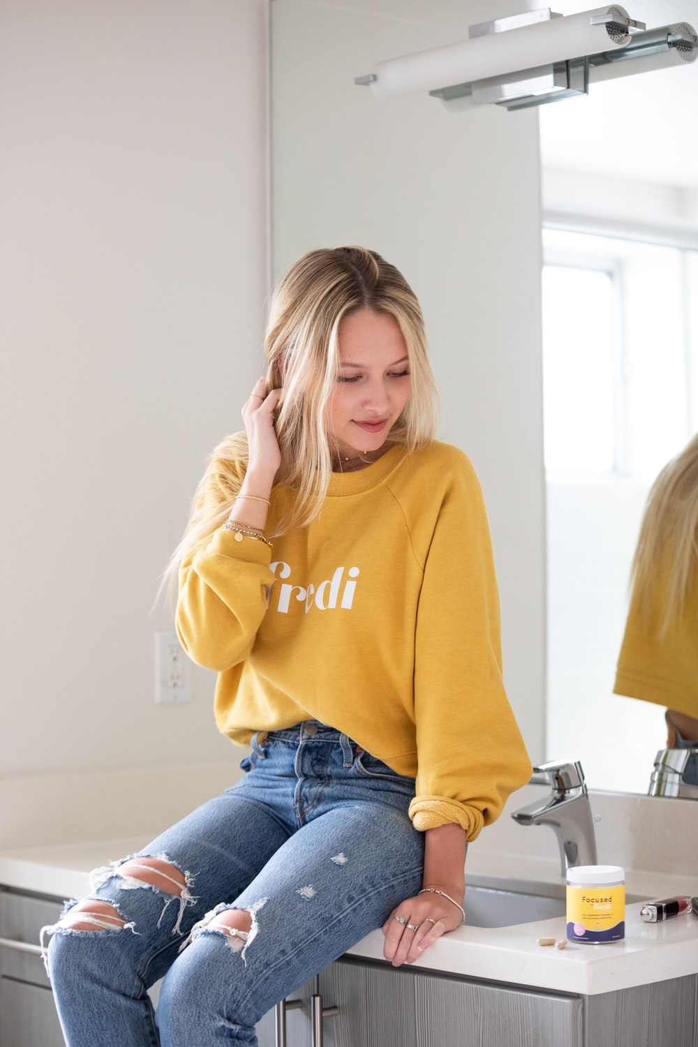 woman in yellow hoodie and blue denim jeans sitting on chair