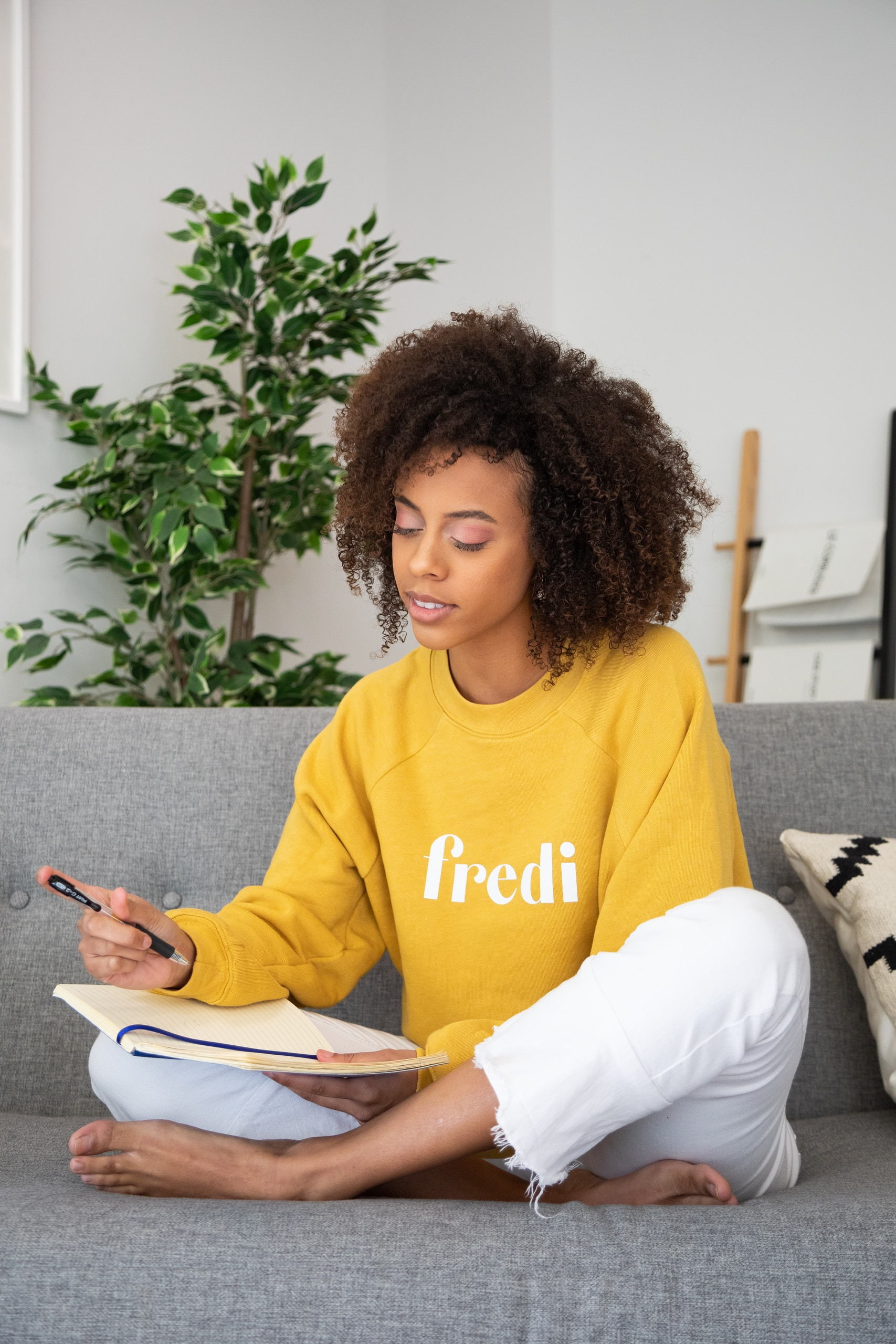 woman in yellow crew neck long sleeve shirt and white pants sitting on white and black