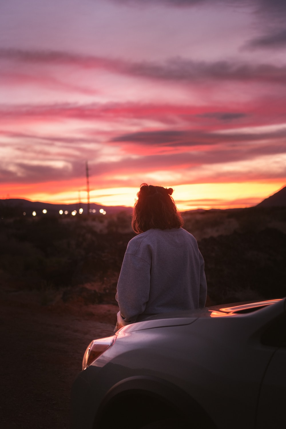 woman in white long sleeve shirt sitting on rock during sunset