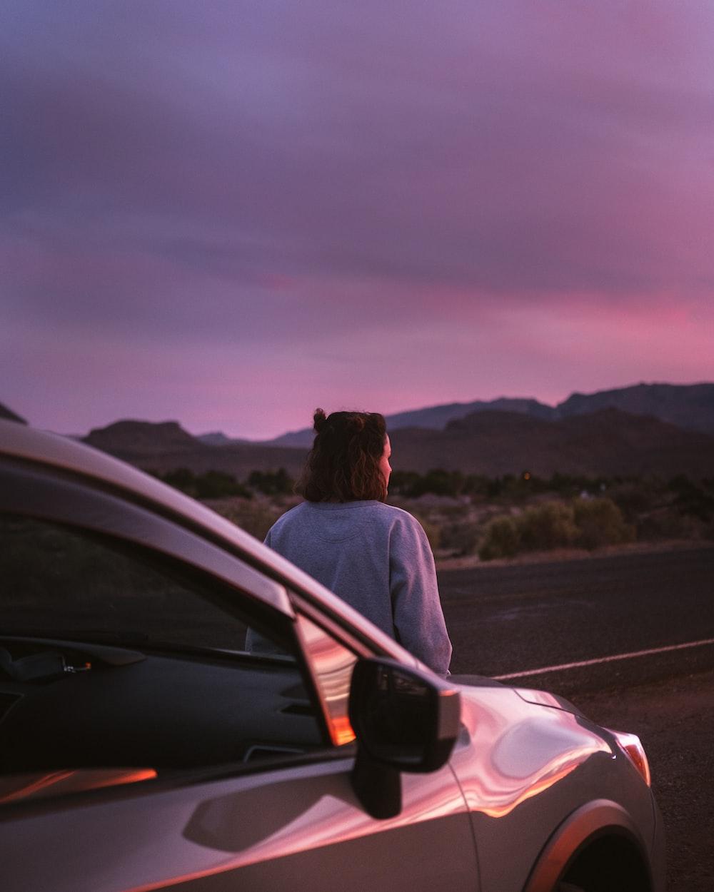 man in white shirt sitting on car hood during daytime