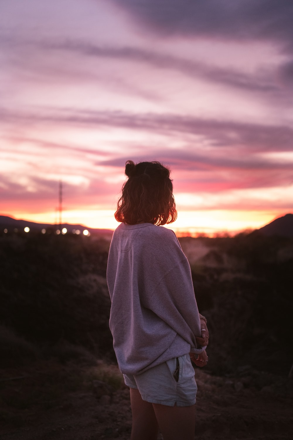 woman in white long sleeve shirt standing on hill during sunset