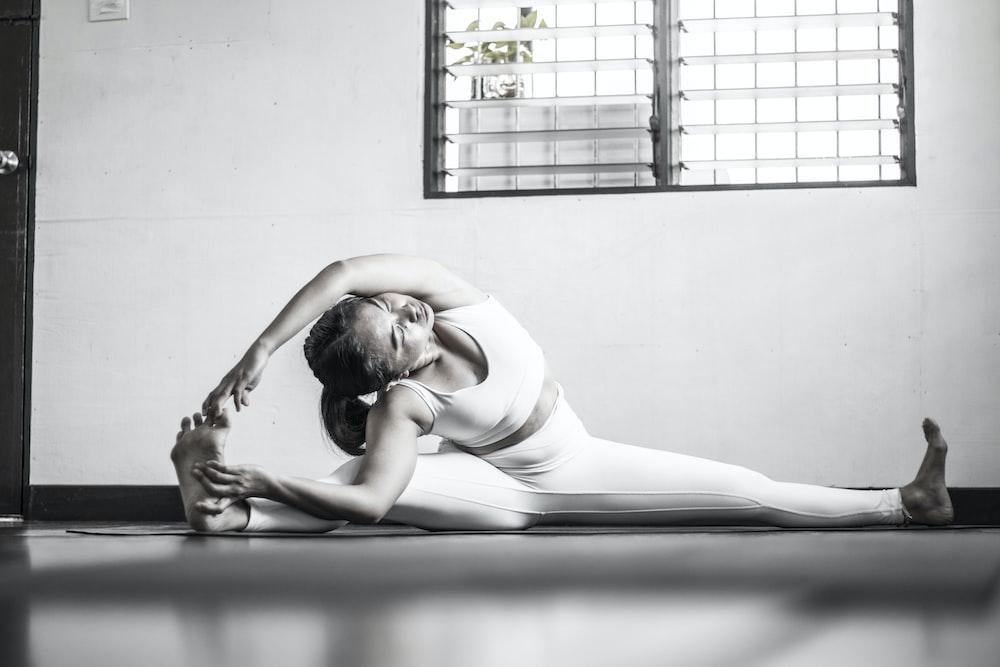 woman in white tank top lying on floor