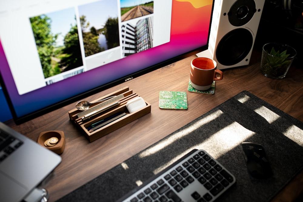 macbook pro beside red ceramic mug