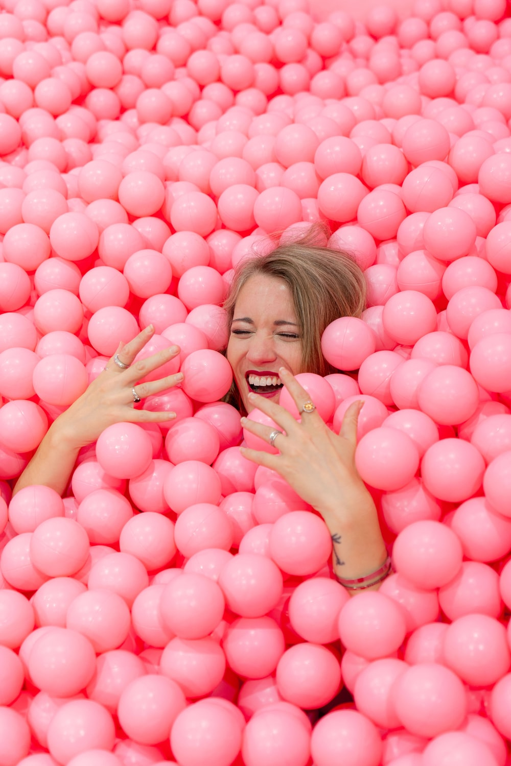 blonde haired woman lying on pink round balls