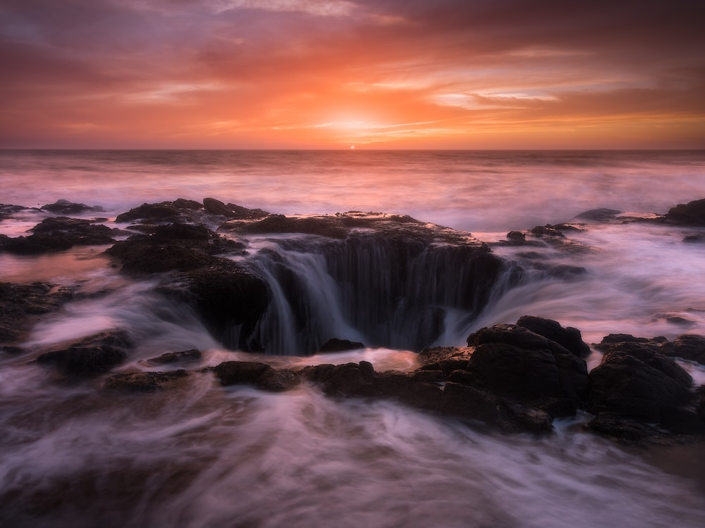 water falls under gray sky during sunset
