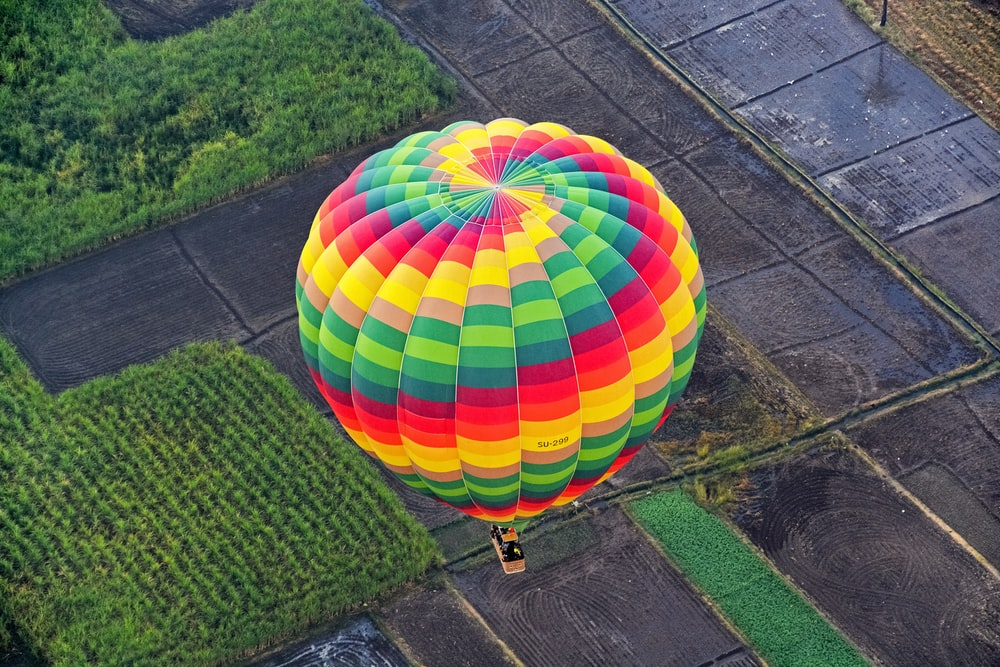 green yellow and blue hot air balloon on green grass