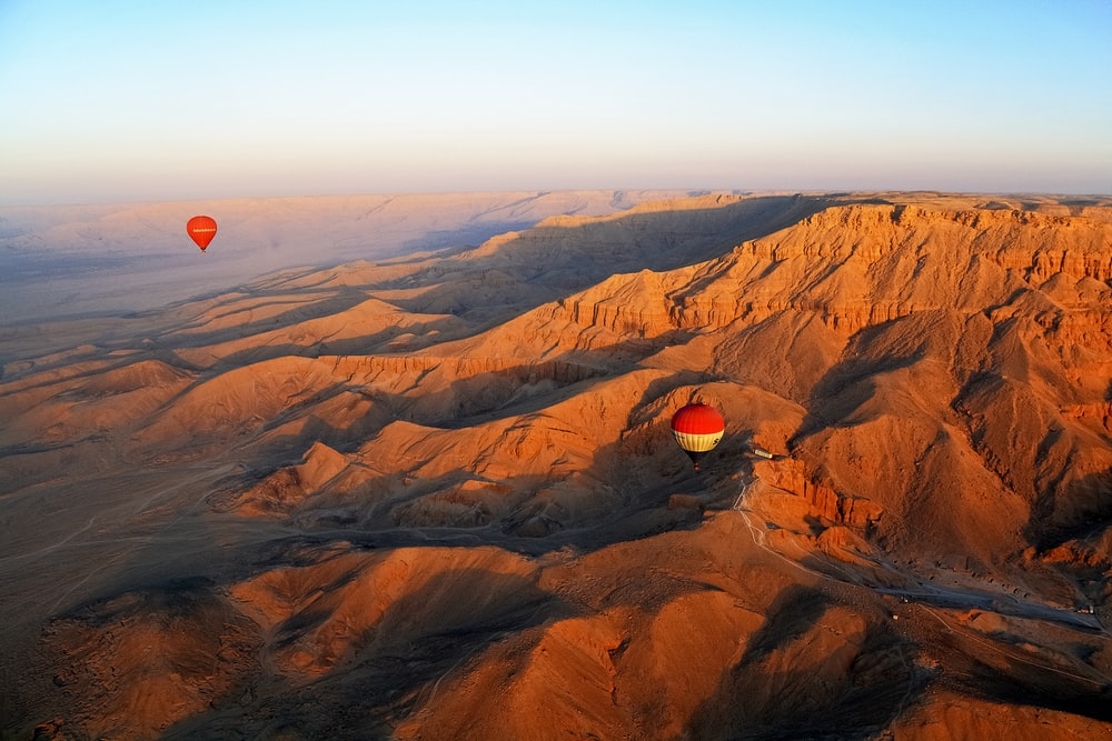 red hot air balloon flying over brown mountains during daytime