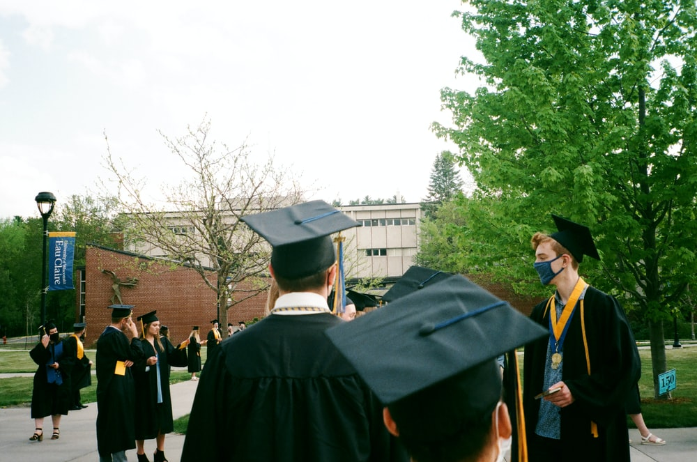 people in academic dress standing near green trees during daytime