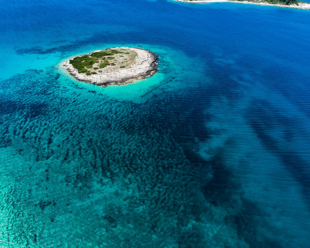 aerial view of green island in the middle of blue sea