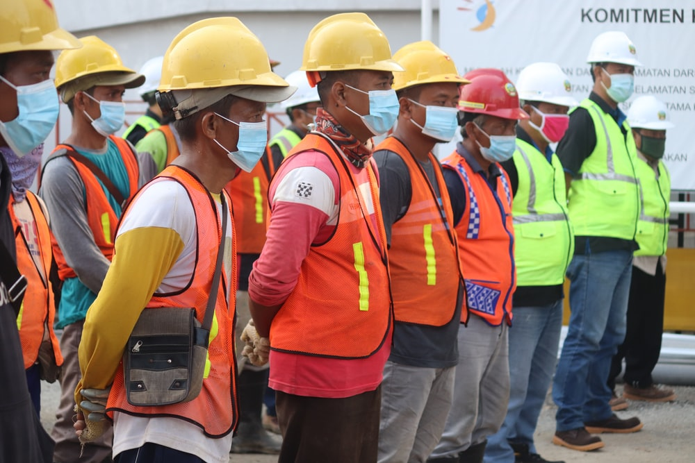 group of people wearing orange and yellow safety vest