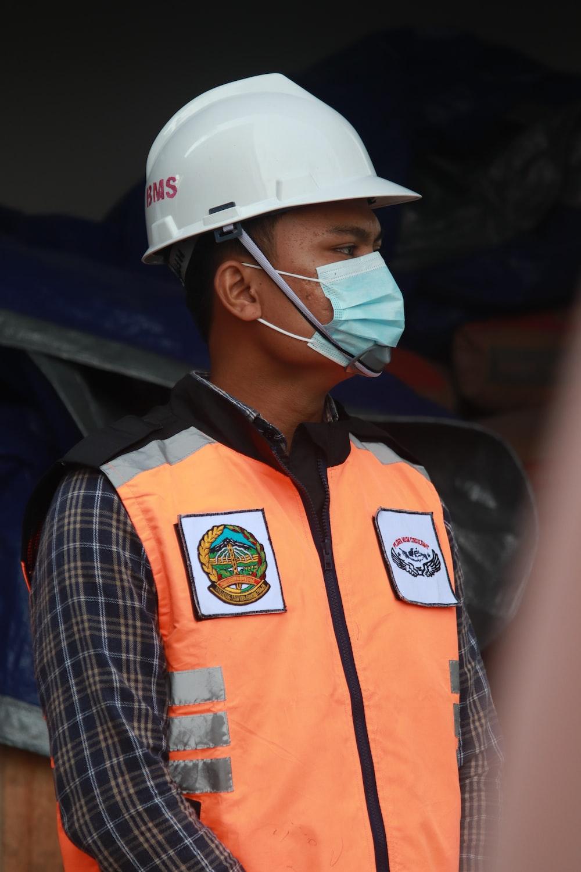 man in orange vest wearing white helmet