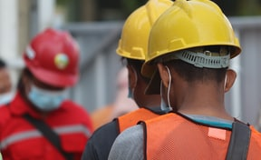 man in orange helmet and black jacket