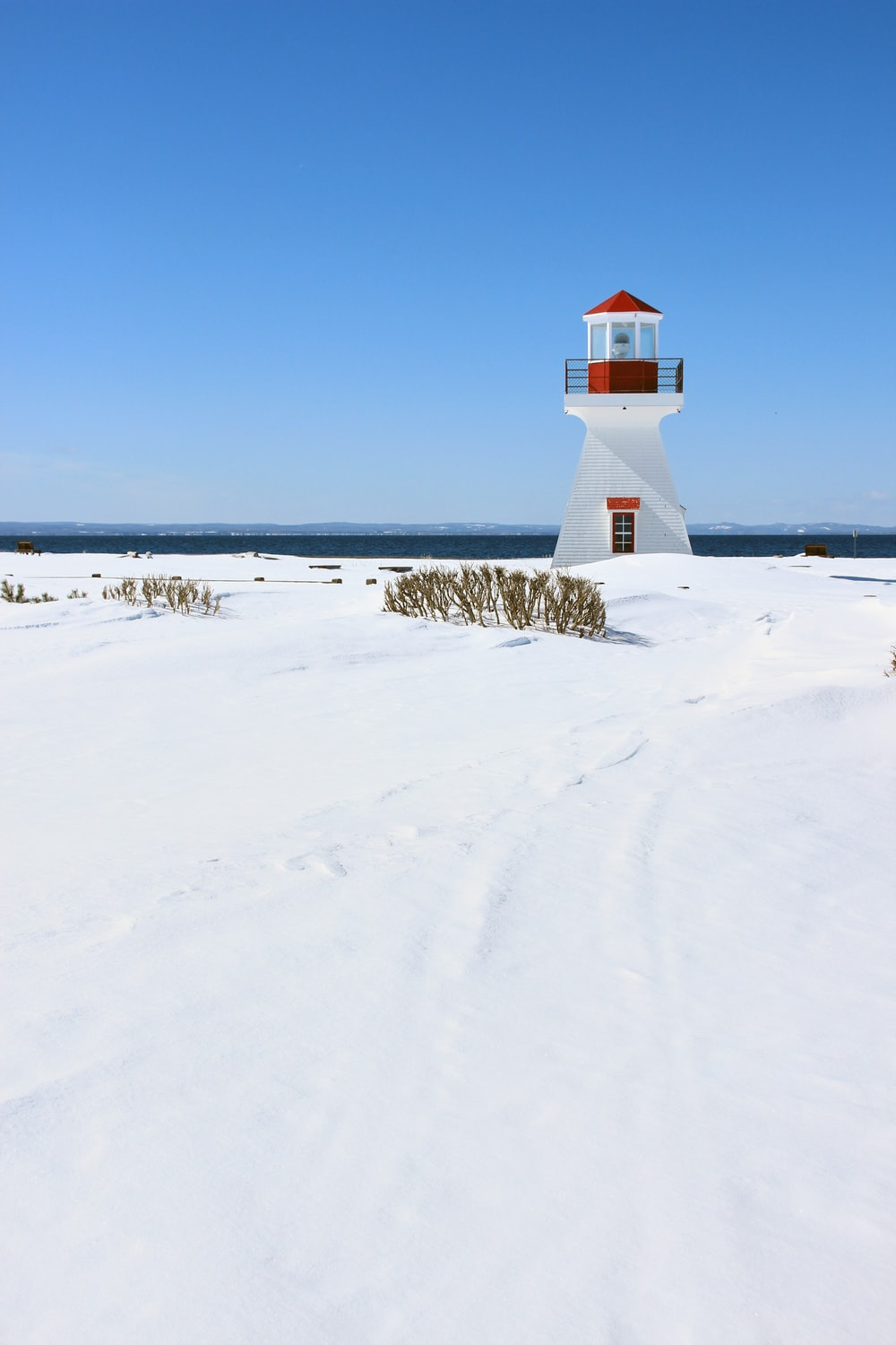 white and red lighthouse on snow covered ground under blue sky during daytime