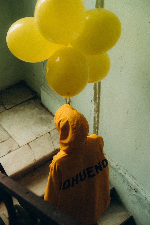 yellow and white balloons on white ceramic tiles