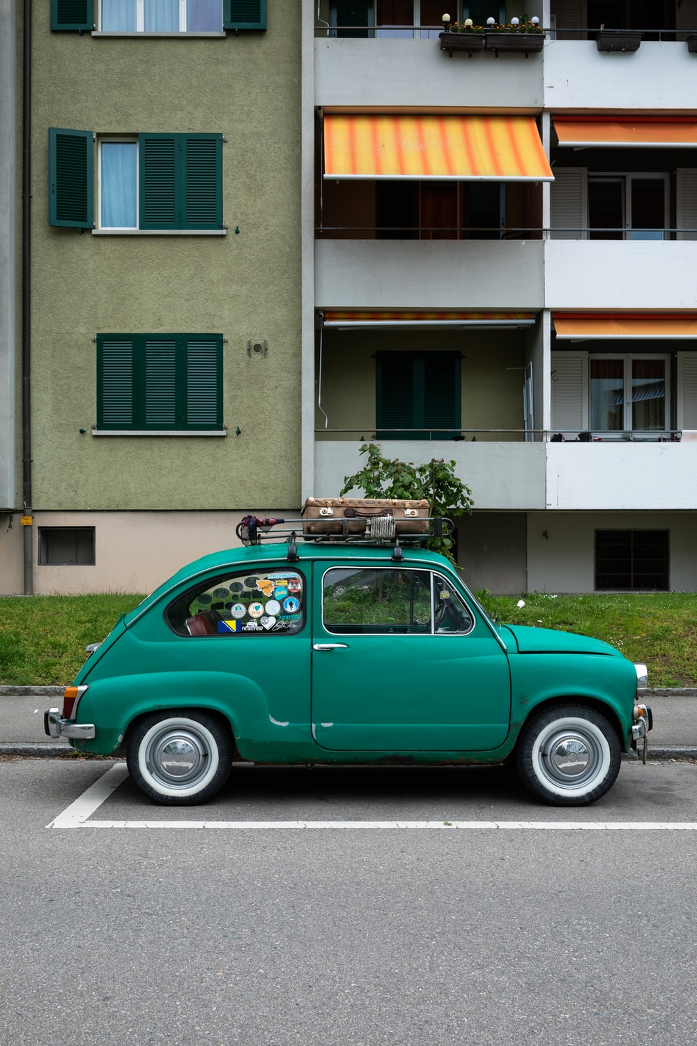green volkswagen beetle parked beside green and white concrete building during daytime