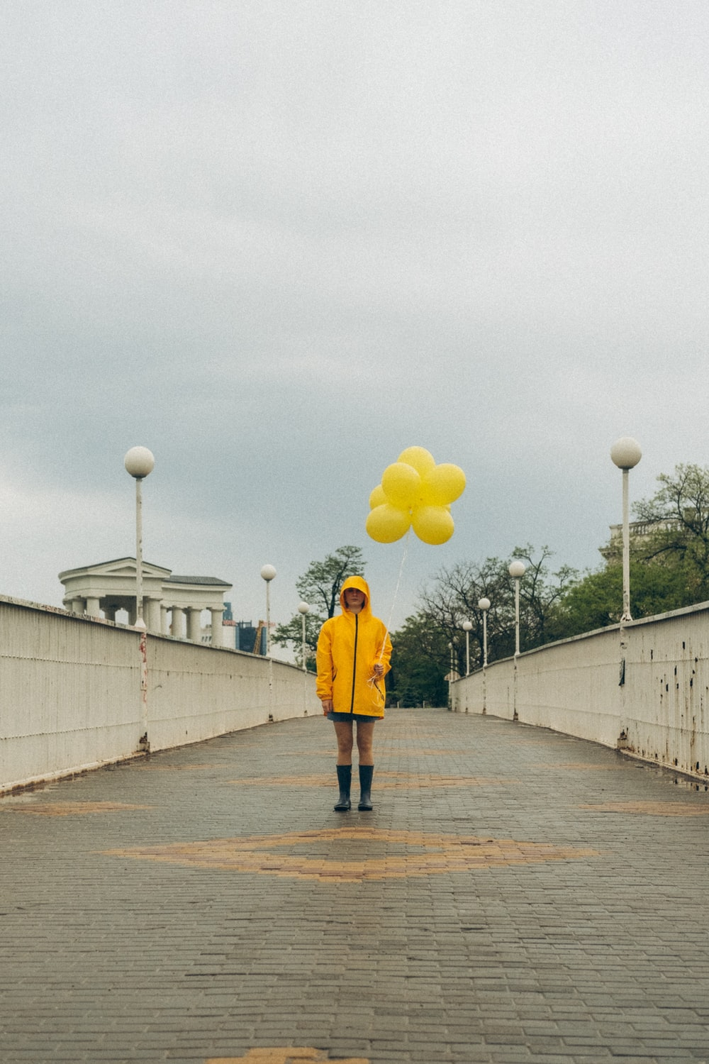 woman in yellow jacket and black pants holding yellow balloons