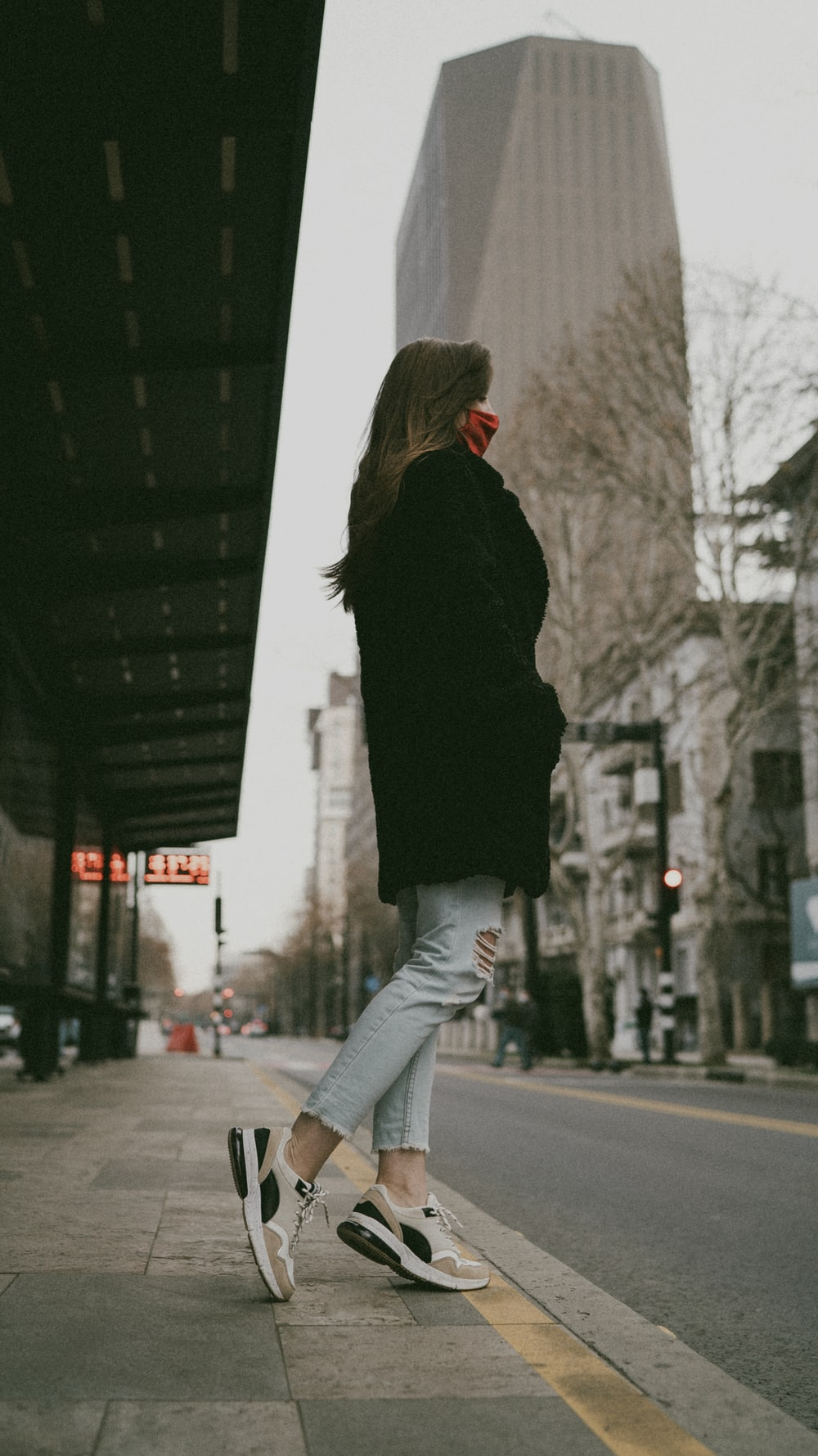 woman in black jacket and gray pants standing on sidewalk during daytime