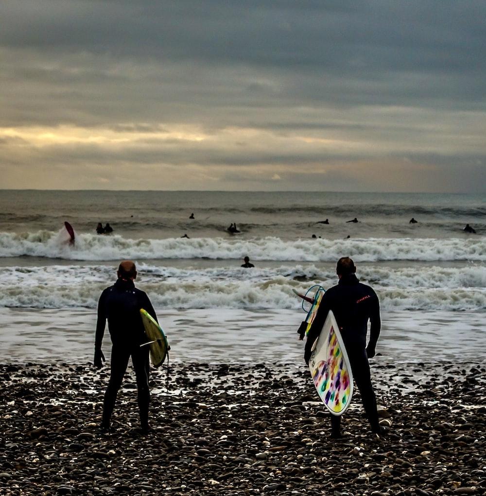 2 men walking on beach during daytime