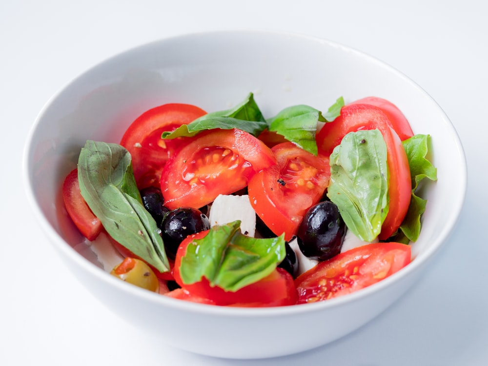red and green bell pepper on white ceramic bowl
