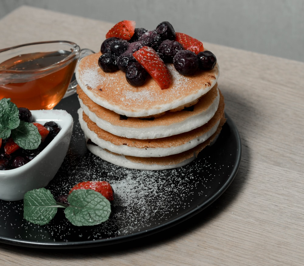 pancakes with berries and berries on black ceramic plate