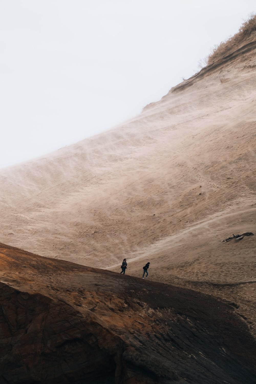 2 people walking on brown rocky mountain during daytime