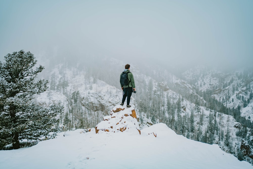 man in green jacket standing on snow covered ground during daytime