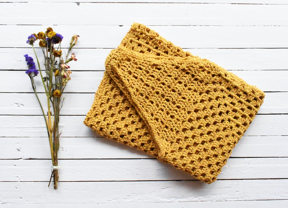 orange knit textile on white wooden table