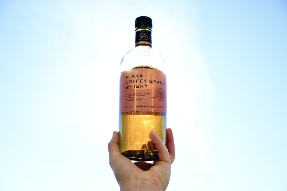person holding white and brown labeled bottle