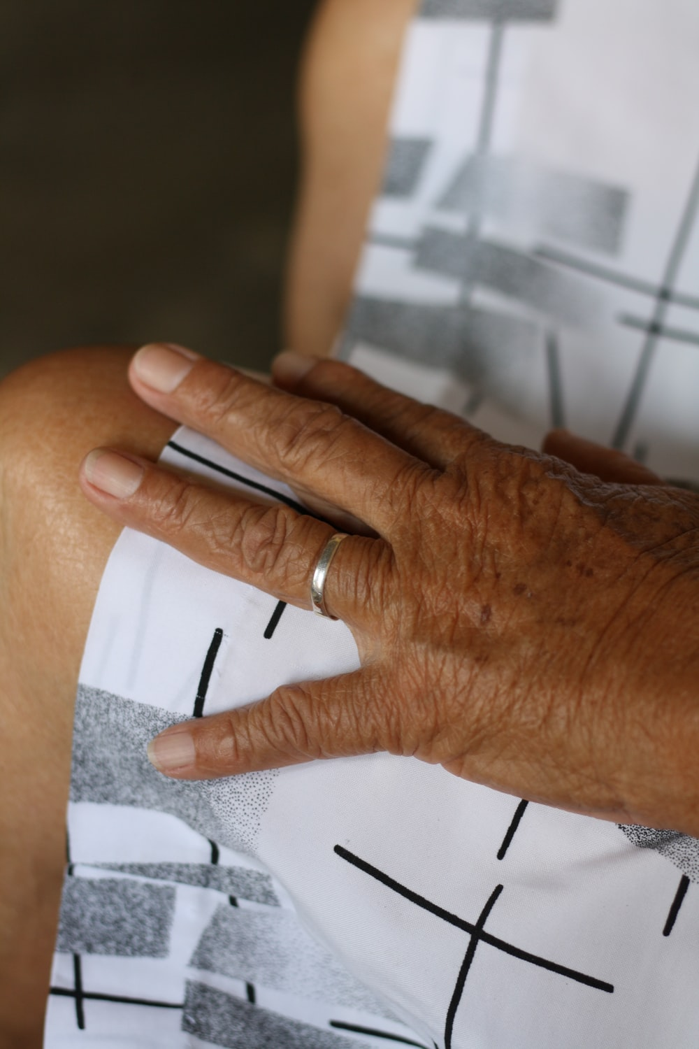 person wearing silver ring on white paper