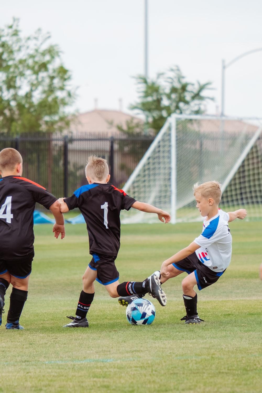 2 men playing soccer during daytime