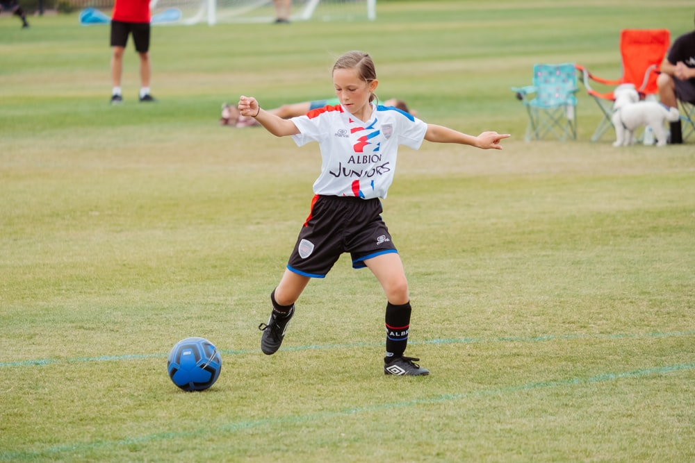 girl in white shirt and black shorts playing soccer on green grass field during daytime