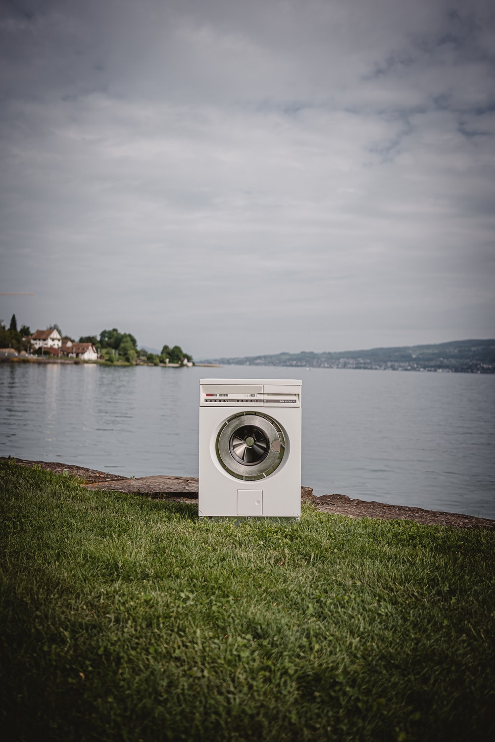 white front load washing machine on green grass field near body of water during daytime
