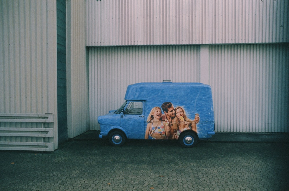 blue and brown car in front of white garage