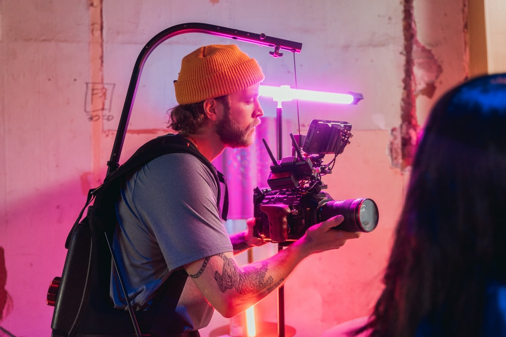 man in brown t-shirt and orange knit cap holding black video camera