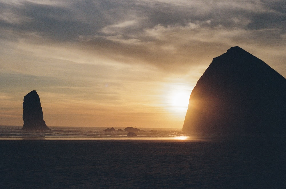silhouette of rock formation near body of water during sunset