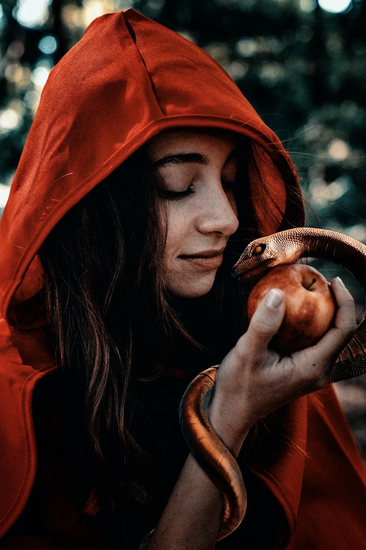 woman in orange hoodie holding brown snake